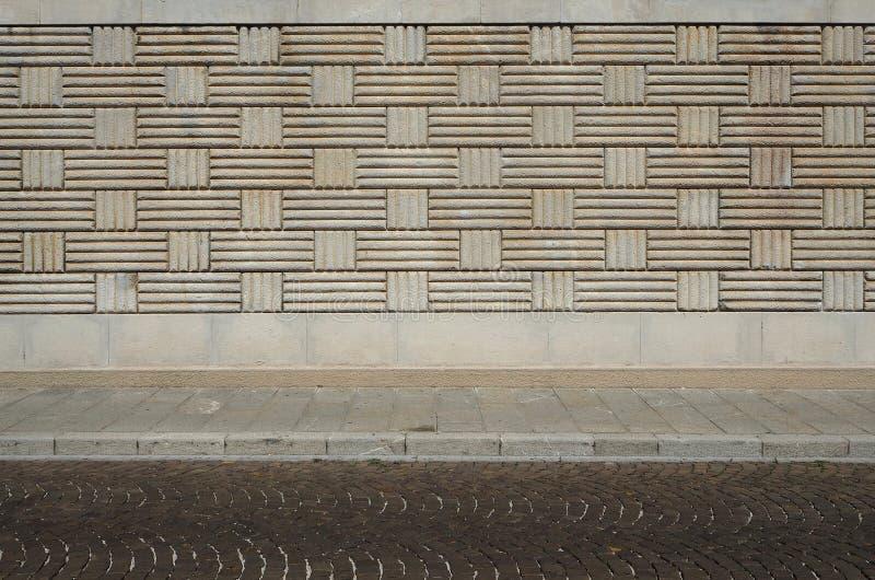 Stedelijke Achtergrond Muur met geometrische patronen, stoep en straat met porfierkubussen stock fotografie