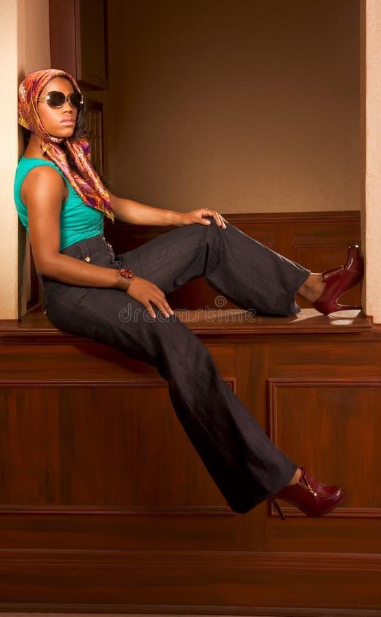 Stedelijke Afrikaans-Amerikaanse vrouw in jeans het zitten stock foto's