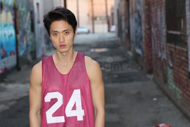 Stedelijke Aziatische mens die dragend mouwloos onderhemd stellen stock afbeelding