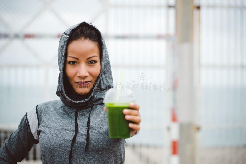 Stedelijke de holdings detox smoothie drank van de geschiktheidsvrouw op trainingrust stock fotografie