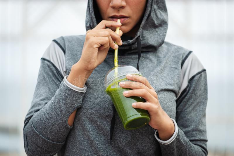 Stedelijke geschiktheidsvrouw die detox smoothie op trainingrust drinken royalty-vrije stock afbeelding