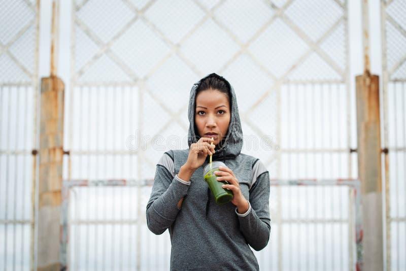 Stedelijke geschiktheidsvrouw die detox smoothie op trainingrust drinken royalty-vrije stock foto's