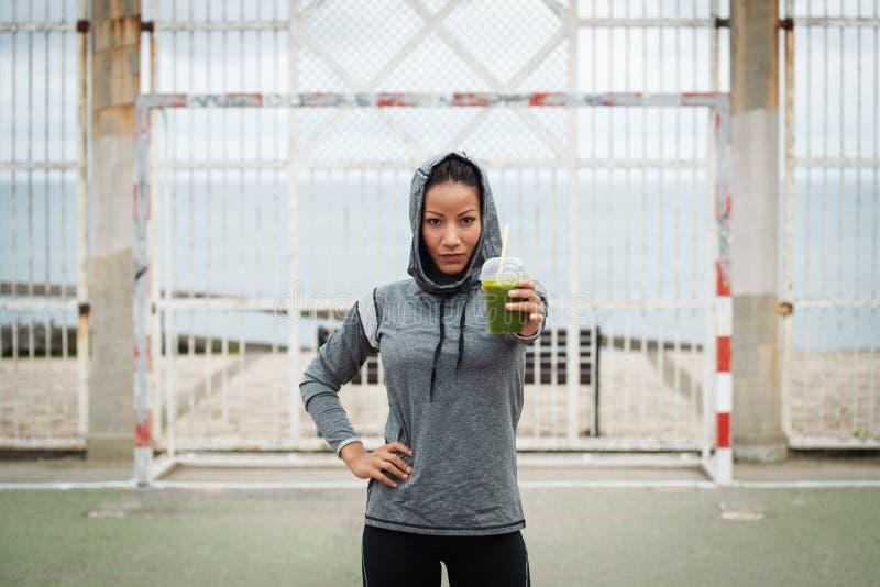 Stedelijke geschiktheidsvrouw die detox smoothie op trainingrust tonen stock afbeeldingen