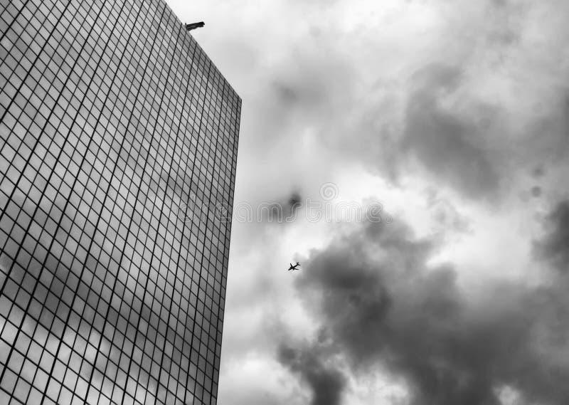 Stedelijke horizon met vliegtuig die over bedrijfswolkenkrabbers vliegen stock afbeeldingen