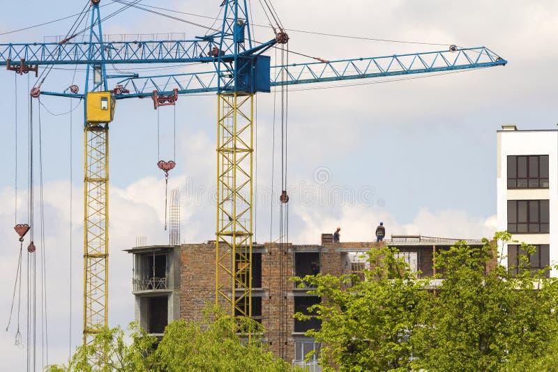Stedelijke mening van silhouetten van twee hoge industriële torenkranen die bij bouw van de nieuwe baksteenbouw werken met arbeid stock afbeelding