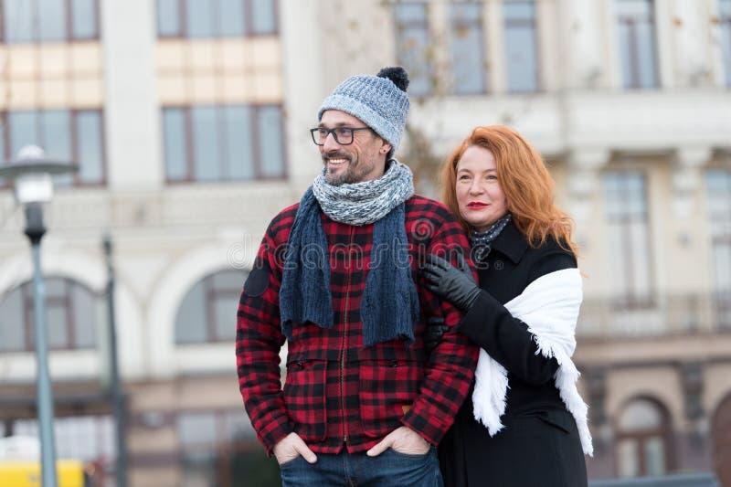 Stedelijke mensen op stedelijke achtergrond Man en vrouwen het vooruitzien Paar die op stadsbus wachten Vrouw die zich achter man stock foto