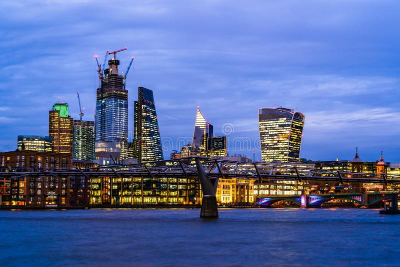 Stedelijke nachtspruit van de Stad van Londen met de Rivier van Theems, de moderne gebouwen en de Milenium-Brug stock foto