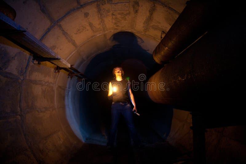 Stedelijke ontdekkingsreiziger met kaars in ondergrondse mededeling, het verwarmen leiding, riooltunnel, enz. stock fotografie