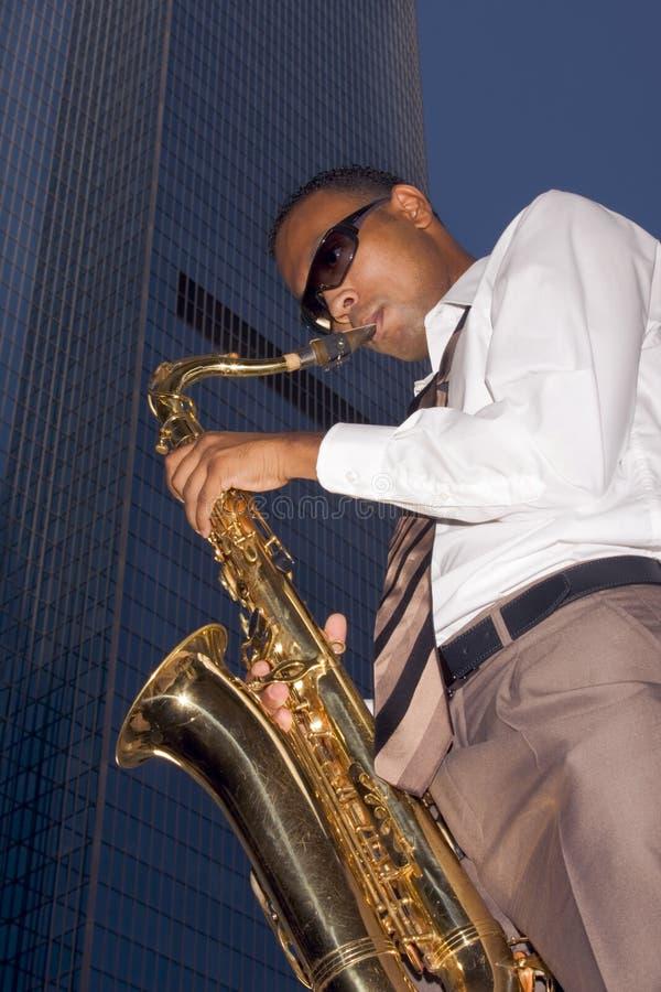 Stedelijke saxofoonspeler op wolkenkrabberachtergrond royalty-vrije stock foto's