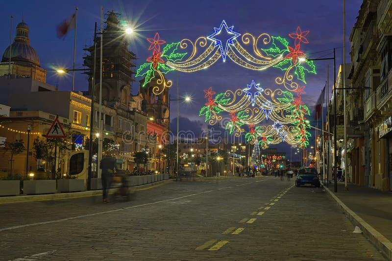 Stedelijke straat met Kerstmisverlichting Van Kerstmislichten en mensen het lopen royalty-vrije stock afbeelding