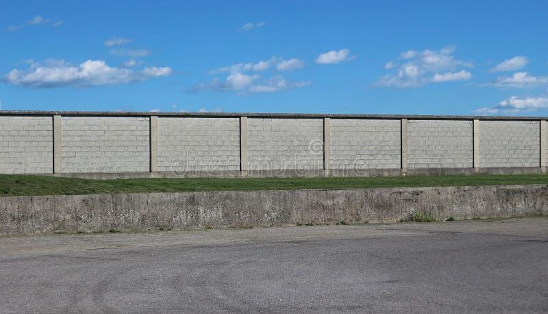 Stedelijke Straatachtergrond Een asfaltweg voor een lange concrete bakstenen muur onder een blauwe hemel met pluizige wolken royalty-vrije stock fotografie