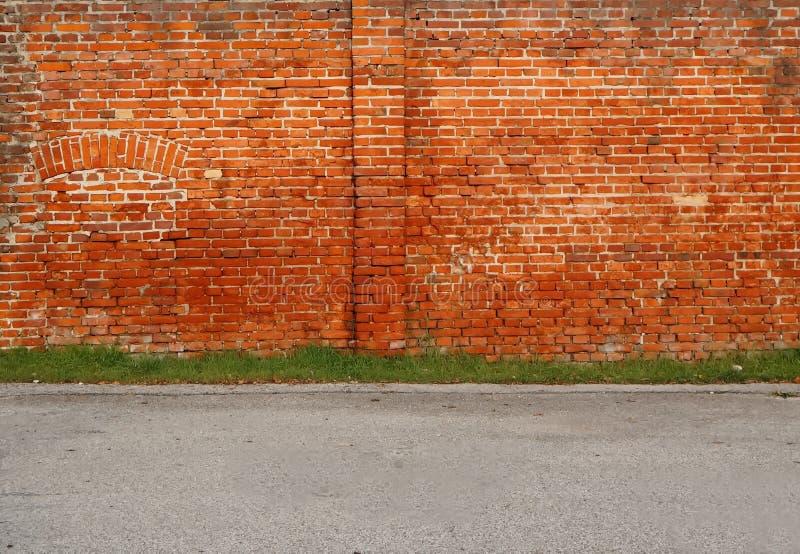Stedelijke Straatachtergrond Oude bakstenen muur, een lijn van gras en een asfaltweg royalty-vrije stock fotografie
