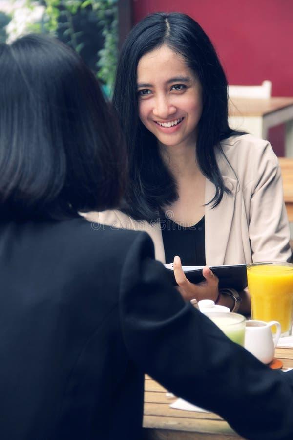 Stedelijke vrouwen die in een restaurant samenkomen stock afbeelding