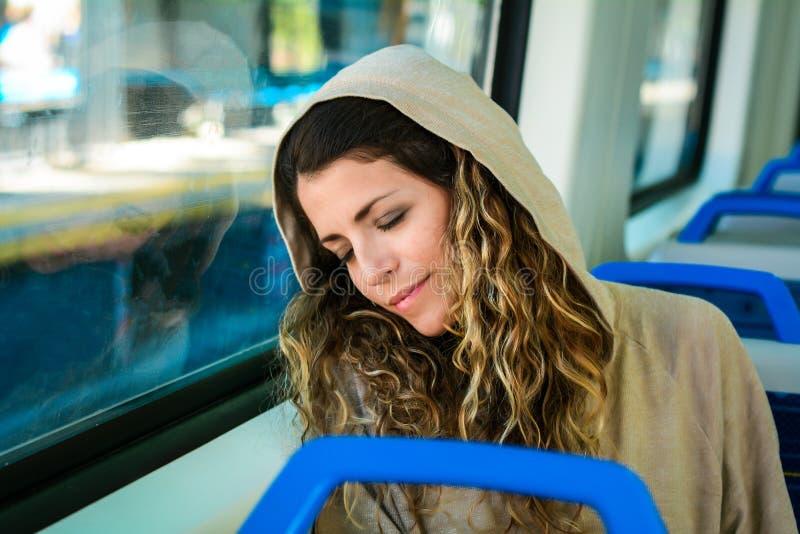 Stedelijke vrouwenslaap in een treinreis naast het venster stock afbeelding