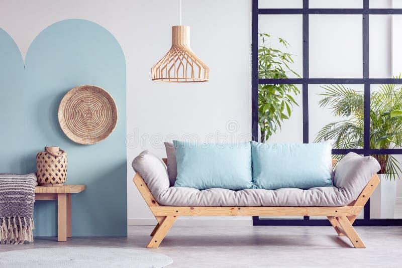Stedelijke wildernis in helder wit en blauw woonkamerbinnenland met Skandinavische futonbank royalty-vrije stock foto's