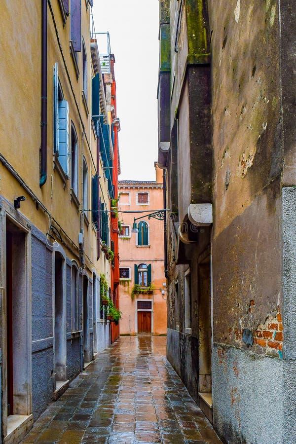 Steeg tussen gotische stijlgebouwen op baksteen/keistraat in Venetië, Italië stock afbeelding