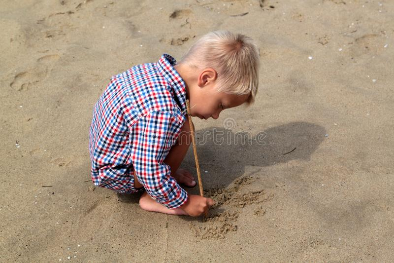 steek weinig jongen in plaidoverhemd trekt aan een stok op het zand op royalty-vrije stock afbeelding