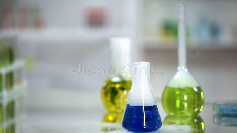 Steekproef van blauwe substantie in fles die zich op lijst van laboratorium bevinden, wasmiddel stock foto