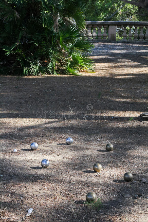 Steel balls for a game of boules. On the ground among light and shadow in a subtropical park stock photo