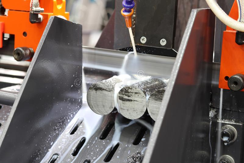 Steel bar cutting by band saw machine. With coolant royalty free stock image