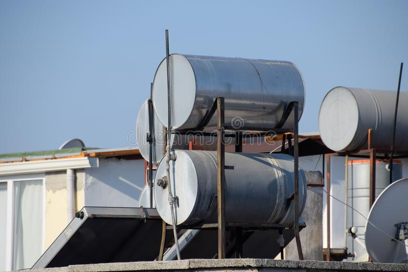 Steel barrels of boilers with water on the roof of a building to heat stock photo