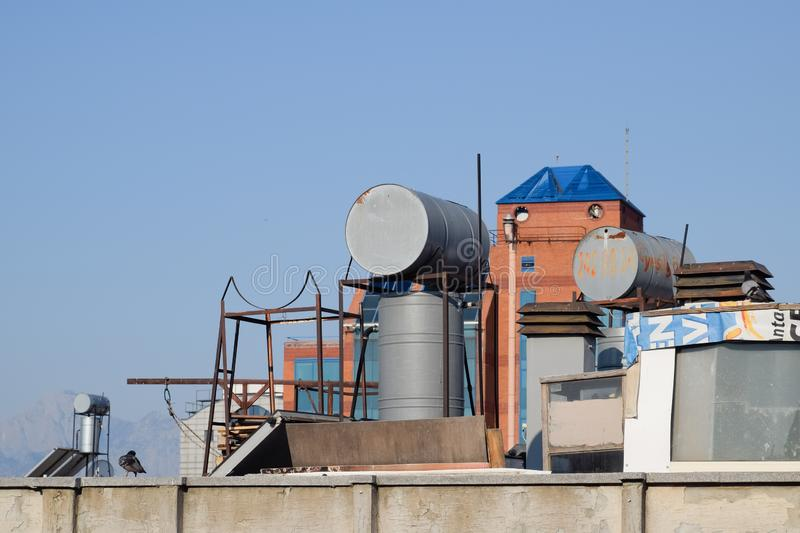 Steel barrels of boilers with water on the roof of a building to heat stock images