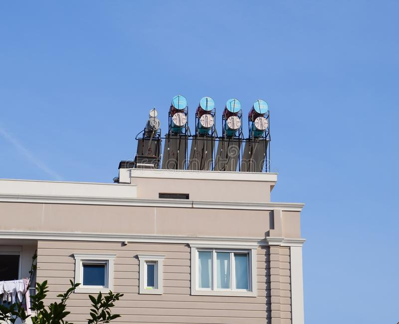 Steel barrels of boilers with water on the roof of a building to heat water. Water heating by the sun and solar panels stock photos