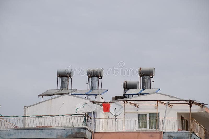Steel barrels of boilers with water on the roof of a building to heat water. Water heating by the sun and solar panels stock photo
