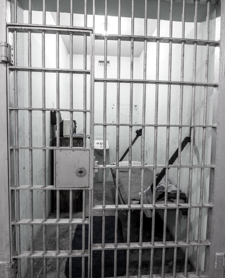 Steel bars over the door of an inmate's prison cell. Old jail cell view through the steel bars showing bed and sink stock photography
