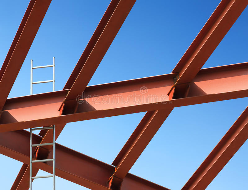 Steel beams and ladder against the blue sky. Fragment construction site royalty free stock photography