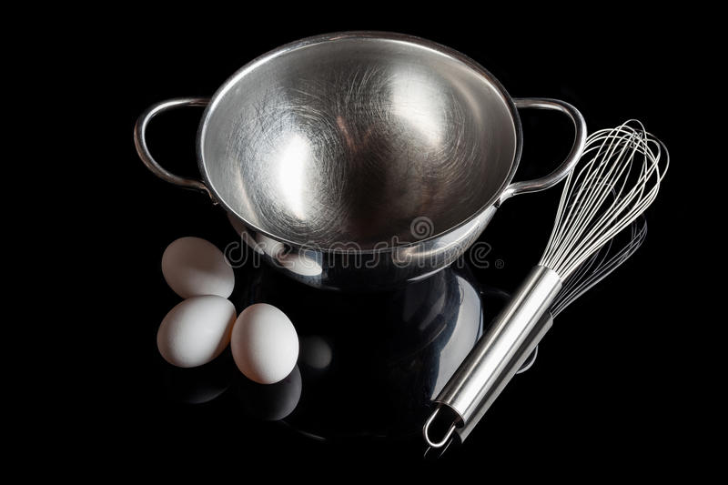 Steel bowl whisker eggs high angle with reflection on black stock photo