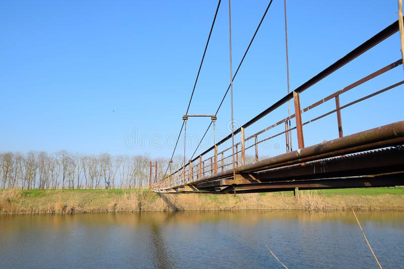 Steel bridge and gas pipeline through irrigation canal stock photography