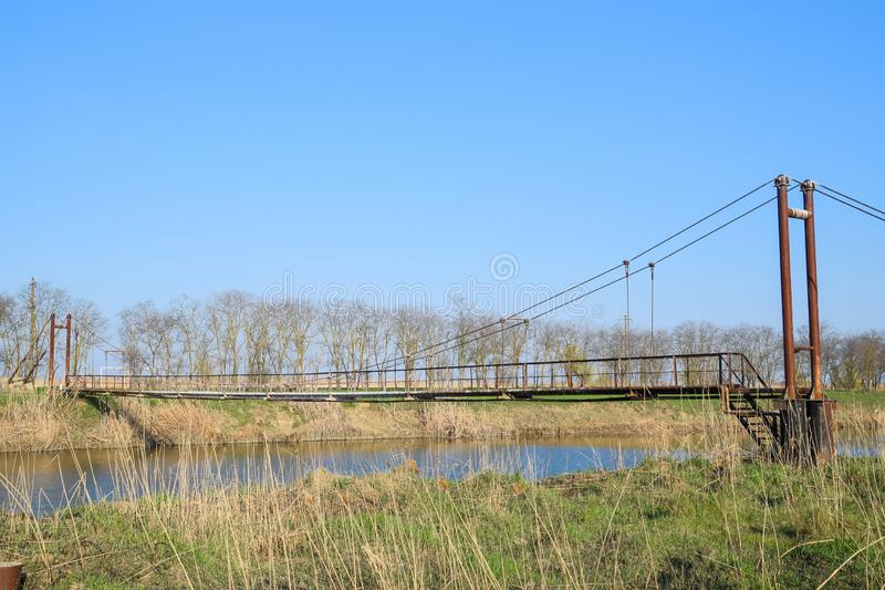 Steel bridge and gas pipeline through irrigation canal stock image