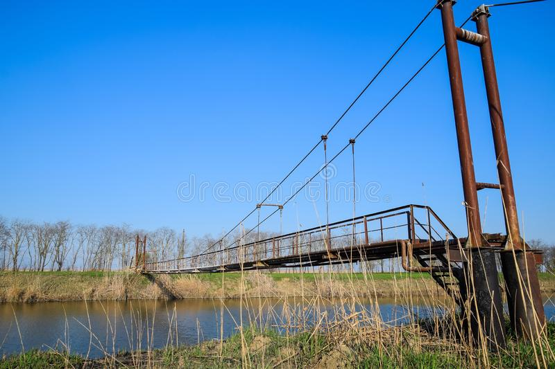 Steel bridge and gas pipeline through irrigation canal royalty free stock photo
