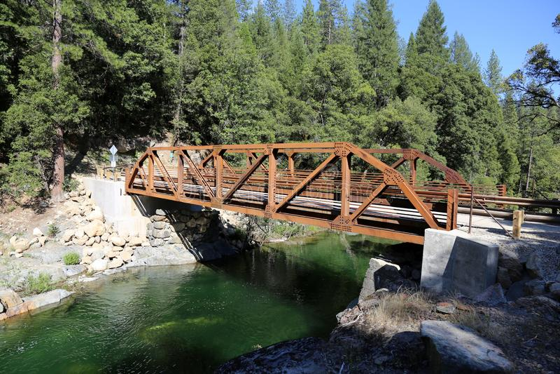 Steel bridge over river with pine trees stock photo