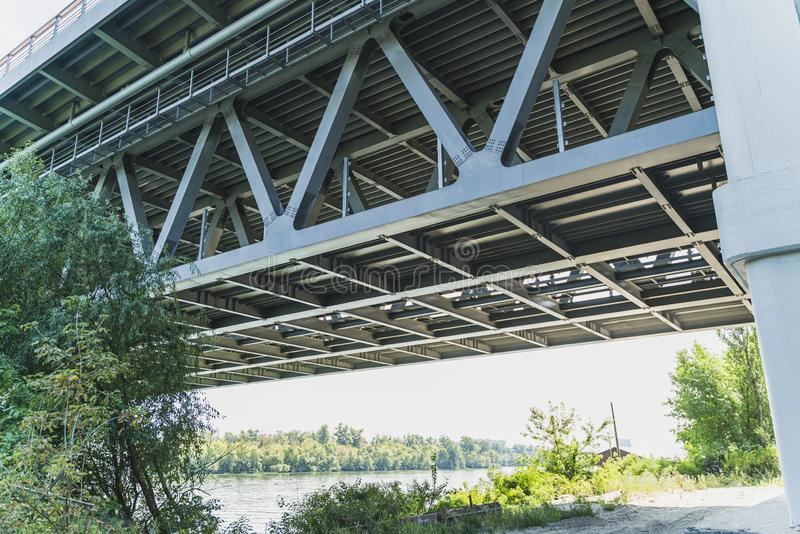 Steel bridge structure, view from below and close up. Big bridge construction across the river in summer, Kiev, Ukraine royalty free stock photo
