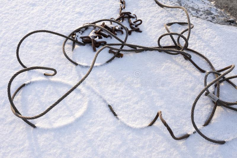 Steel wire rope and chain in snow. Old steel wire rope and rusty chain tangled in snow stock photos