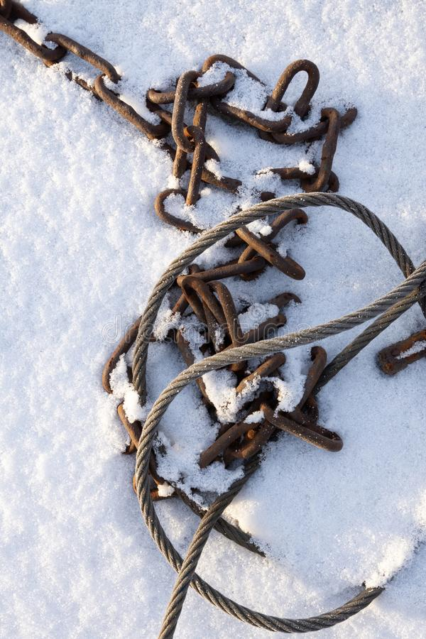 Steel wire rope and chain in snow. Old steel wire rope and rusty chain tangled in snow royalty free stock photos