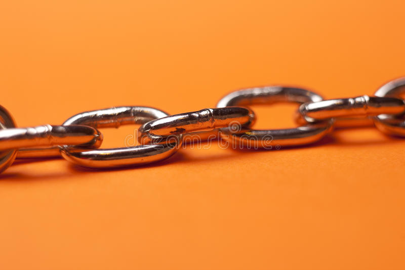 Steel Chain. A closeup view of the links of a steel chain, on orange surface stock photos