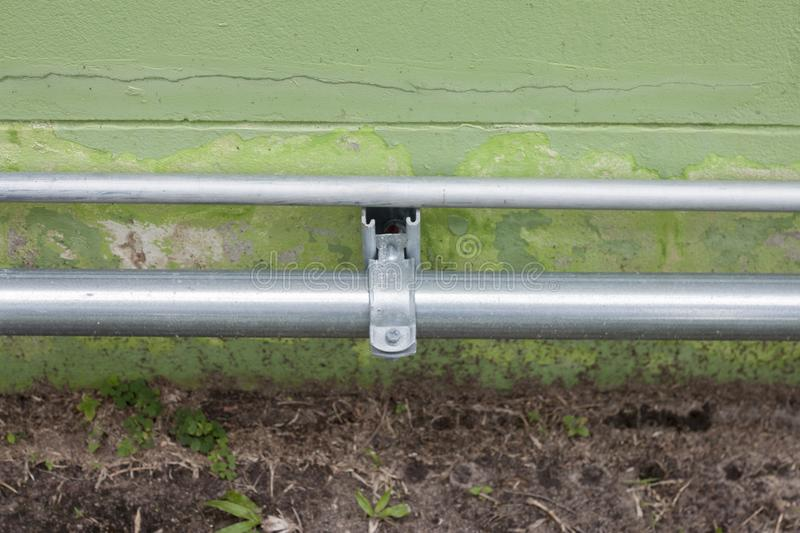 Steel conduit on the wall. Conduit Pipe Installed on a green flap above the ground royalty free stock photos