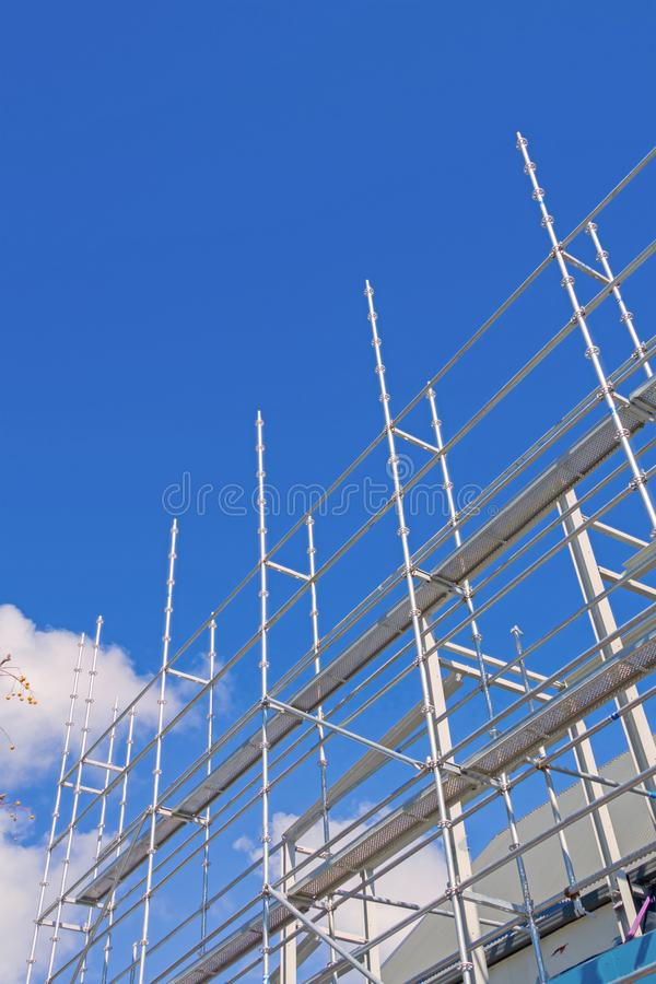 Steel construction scaffolding. Erected and rising into sky with lens flare from sun stock photography