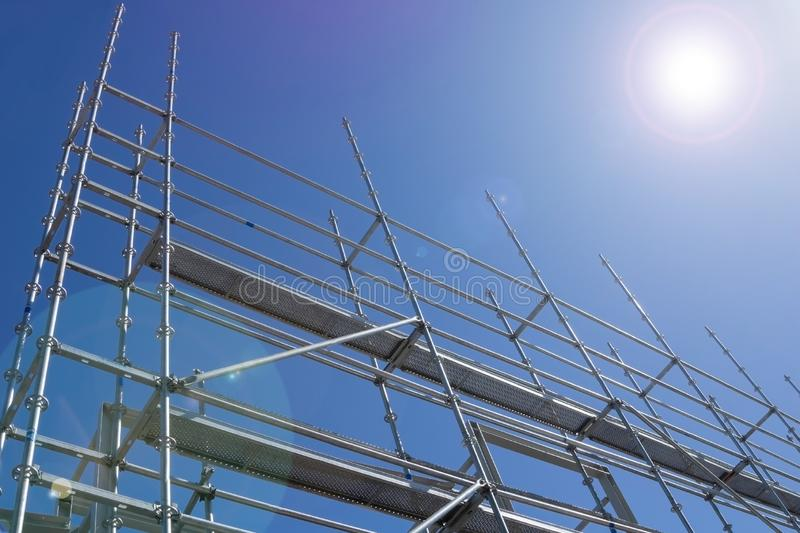 Steel construction scaffolding. Erected and rising into sky with lens flare from sun royalty free stock photos