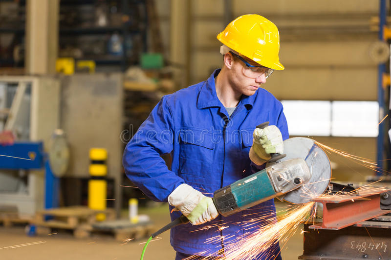 Steel construction worker cutting metal with angle grinder stock photography