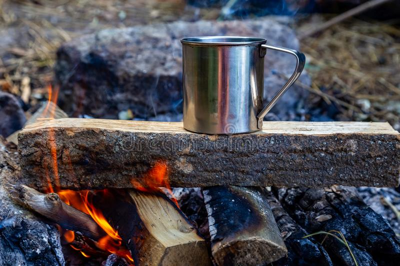 Steel cup on an open fire in nature.  royalty free stock photos