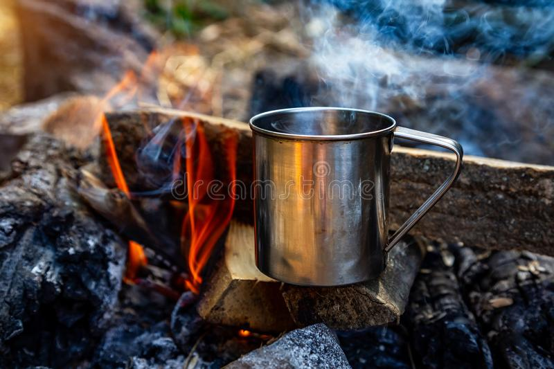 Steel cup on an open fire in nature.  royalty free stock images