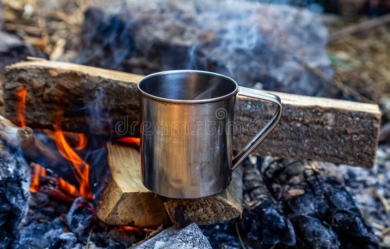 Steel cup on an open fire in nature. Cooking on fire. Camping in summer.  royalty free stock image