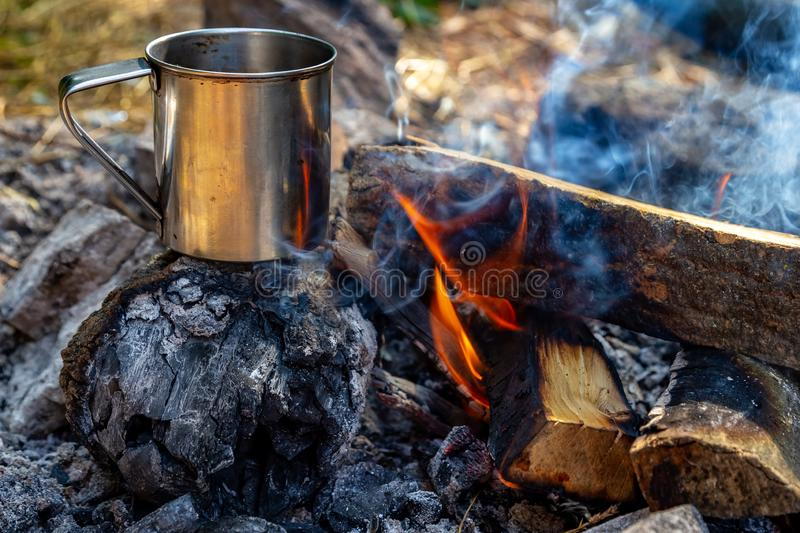 Steel cup on an open fire in nature. Cooking on fire. Camping in summer.  stock photography