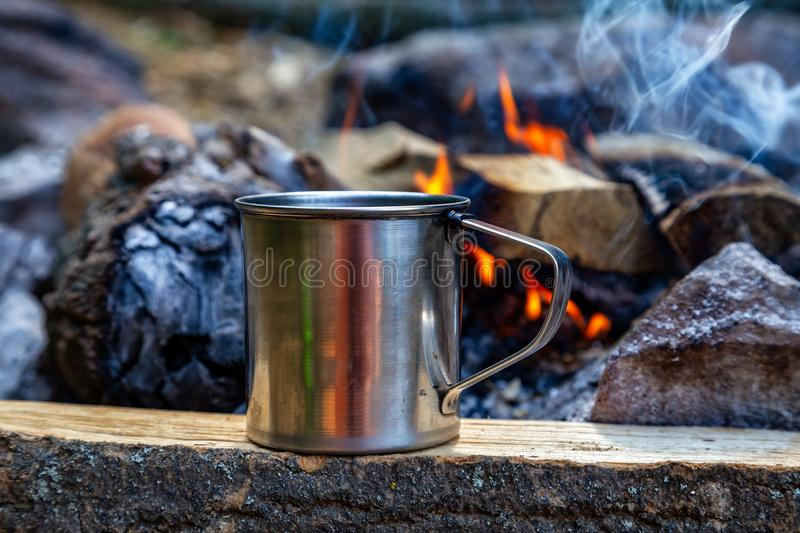 Steel cup on an open fire in nature. Cooking on fire. Camping in summer.  stock image