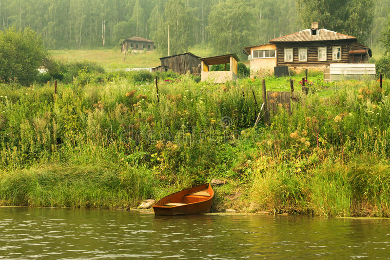 Steel fishing rowboat in red next to a wooden house. Russia, Ural royalty free stock image
