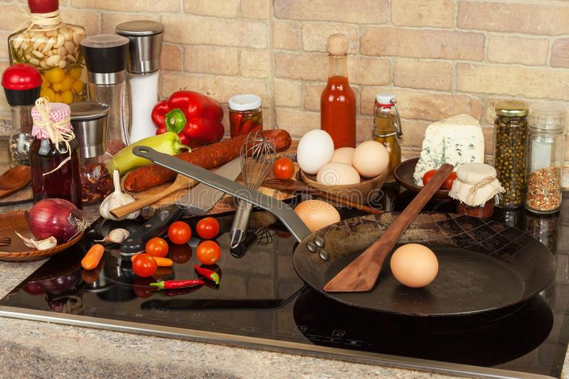 Steel frying pan on the stove. Kitchen utensils. Preparation of egg omelette. Diet food. royalty free stock images